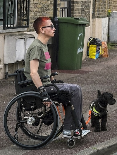 Colour photograph of a white woman with short red hair, sitting in the street in a manual wheelchair accompanied by a small black dog in a hi-vis jacket