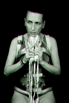 Black and white photo showing ju90, dressed in a her decorated spinal brace, a silver vest and black g-string, sitting holding her ballet shoes in front of her and looking into the distance with a determined expression on her face.