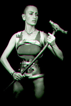 Black and white photo showing ju90, dressed in her decorated spinal brace, a silver vest and black g-string, standing holding her walking stick in front of her like a weapon and looking down at it.