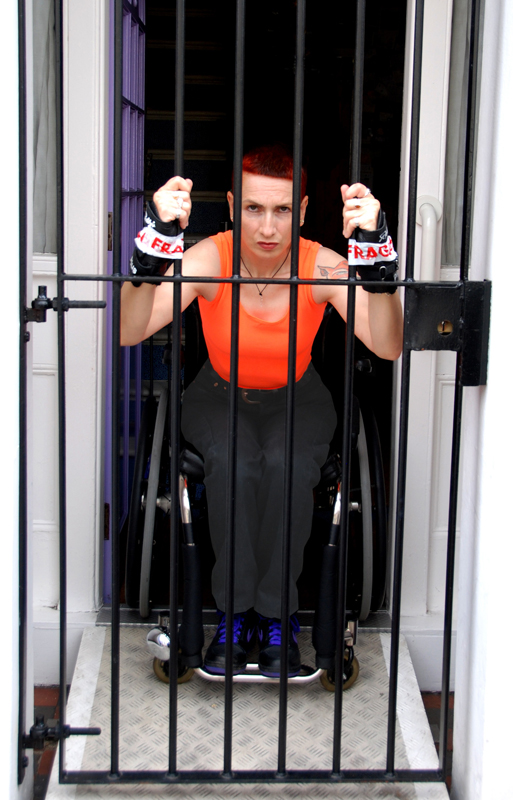 Image of a woman with short red hair, dressed in an orange vest, black trousers and black trainers with purple laces. Shes is sitting in a wheelchair in front of an open door but behind a security gate to which her wrists are tied with Fragile tape.