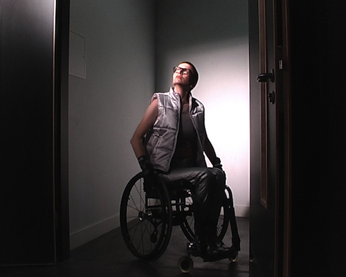 Video still of a woman with short red hair and black-framed glasses, dressed in a silver waistcoat and trousers and sitting in a manual wheelchair, looking upwards