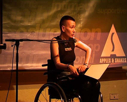 Photograph of ju90 performing in wheelchair, with Apples and Snakes banner behind