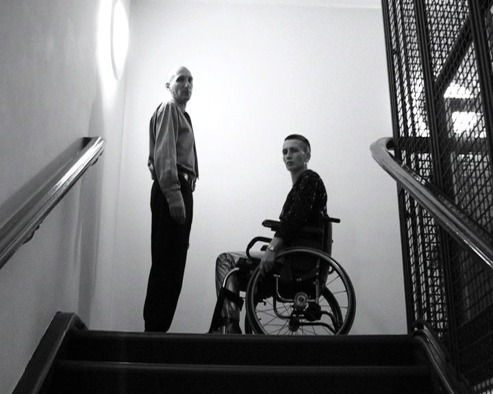 Black and white video still of two people looking down from the top of a staircase - a woman using a manual wheelchair, facing a man who is standing.